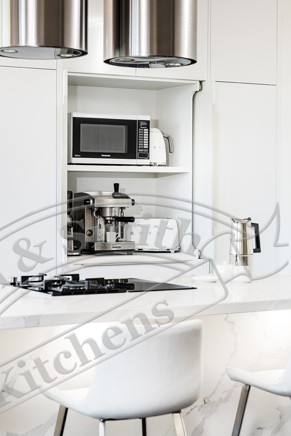 Modern kitchen with an appliance cabinet fitted with pivot sliding doors.